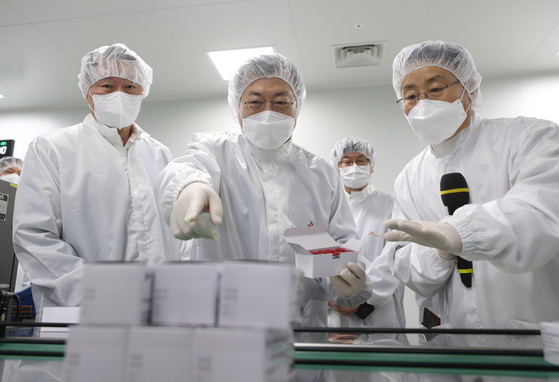 President Moon Jae-in, center, and SK Group Chairman Chey Tae-won, left, look at vaccine development facilities during a visit to SK Bioscience's factory in Andong, North Gyeongsang. [JOINT PRESS CORPS]