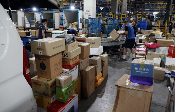 Employees at a logistics center in Songpa District, Eastern Seoul, sort parcels on June 9. [YONHAP]