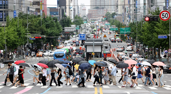 Pedestrians at a crosswalk in the Hongdae area in Mapo District, western Seoul, protect themselves from the rain on Saturday as the rainy season started. [YONHAP]