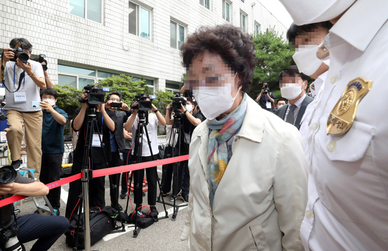 Former Prosecutor General Yoon Seok-youl's mother-in-law, center, enters the Uijeongbu District Court on Friday to attend the sentencing of her trial. She was convicted of fraud and medical law violations and sent to a prison to serve three years. [YONHAP]