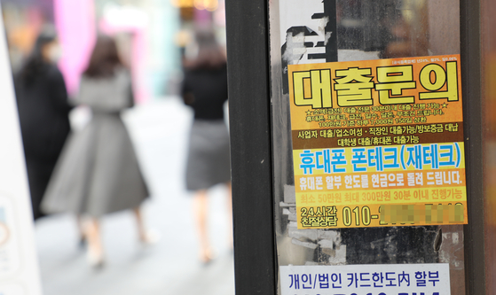 Business cards of illegal loan sharks are stuck at a store entrance in Seoul. [YONHAP]