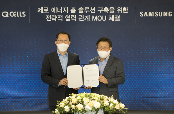 Hanwha Q Cells CEO Kim Hee-chul, left, poses for a photo with Lee Jae-seung, head of Samsung Electronics' home appliance unit, after signing a memorandum of understanding on July 2. [SAMSUNG ELECTRONICS]