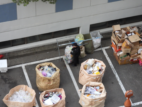 A security guard looks through the recyclable trash collected in an apartment complex in Yeongdeungpo District, western Seoul, on June 19. [KANG CHAN-SU]