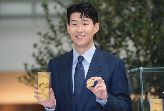 Tottenham Hotspur Son Heung-min holds up a commemorative coin and plaque issued by the Korea Minting and Security Printing Corporation (Komsco), at The Hyundai Seoul, Yeouido, on Monday . The commemorative coin, celebrating the 28-year-old's career so far, is available to purchase on the Komsco website. [YONHAP]
