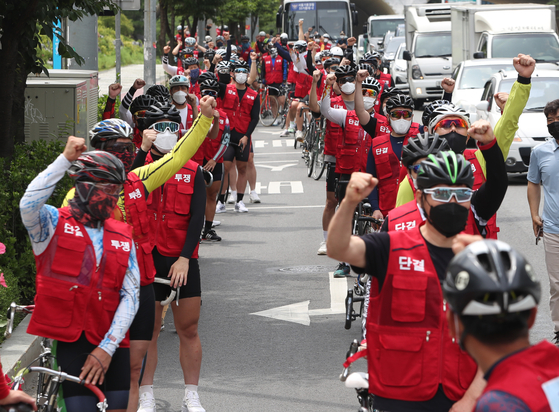 Professional cyclists rally during a ride through the streets of Guro District, southwestern Seoul, on Monday, calling on the Korea Sports Promotion Foundation to guarantee minimum livelihood for bicycle racers. They are suffering from financial difficulty as professional bicycle racing events have been suspended because of Covid-19 pandemic. [NEWS1]