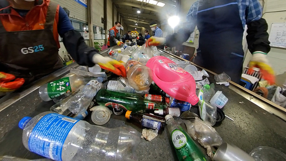 Recyclable waste being sorted out by workers at a center in Gimpo. [WANG JUN-YEOL]