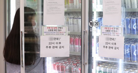 A customer buys beer at a convenience store located at the Han River park in Yeouido on Tuesday. A notice is posted on the refrigerator that announces that no alcohol will be sold after 10 p.m. The Seoul city government has banned alcohol consumption after 10 p.m., including at the Han River, as the number of people infected with Covid-19 is rising fast. On Tuesday, 1,006 new infections were confirmed, the highest in six months. [NEWS1]