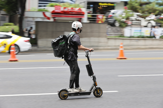 Food being delivered via e-scooter in Seoul. Food orders have surged as people continue to spend time at home due to Covid-19, contributing to online purchase breaking 16 trillion won for the first time in May. [YONHAP]