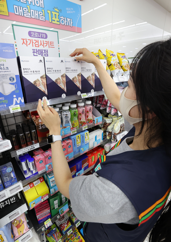A store employee stacks Covid-19 self testing kits at a 7-Eleven store in central Seoul on Wednesday. The number of people confirmed to have contracted Covid-19 reached the second-highest daily figure on Tuesday, raising concerns that the Delta variant is spreading rapidly in Korea. [YONHAP]