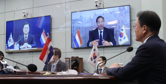 """Korean President Moon Jae-in, right, and Dutch Prime Minister Mark Rutte, on right screen, hold a virtual summit in the Blue House on Wednesday. The two leaders agreed to strengthen cooperation on the semiconductor supply chain, """"recognizing each other as core partners in the field of semiconductors,"""" according to their joint press statement. [YONHAP]"""