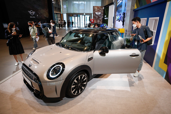 Customers check out a newly upgraded Mini Cooper displayed at State Tower Namsan in central Seoul on Wednesday. BMW Korea unveiled three new Mini cars — the Mini 3-door, Mini 5-door and Mini Convertible. The automaker will be holding a joint campaign with coffee franchise Starbucks under the slogan: ″We are different, but pretty good together.″ Korea is the only country where the two have collaborated. [NEWS1]