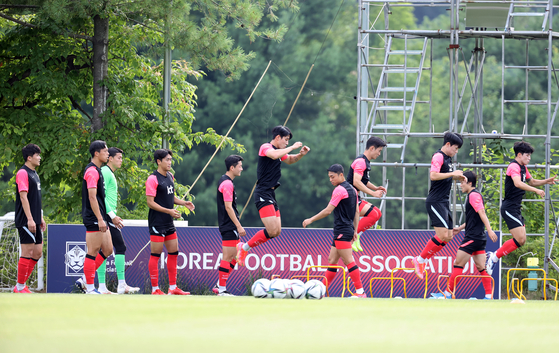 Olympic football team players warm up at the National Training Center in Paju, Gyeonggi on Tuesday. Korea will start its Olympic football campaign in two weeks on July 22 with a game against New Zealand at 5 p.m. [YONHAP]