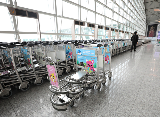 Baggage carts stand empty at a passenger terminal in Incheon International Airport on Wednesday. Despite expectations that the travel industry would begin to recover as inoculations increase, the increasing number of Covid-19 cases is expected to again stall overseas travel. [NEWS1]