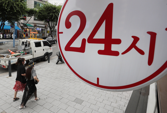 A sign at a restaurant in Hongdae, Seoul, on Wednesday says it is opened 24 hours. However, as the number of people confirmed with Covid-19 has exceeded 1,200 on Tuesday, the government extended its social distancing that limit business hours to 10 p.m. for another week. KDI warned that the recent surge in Covid-19 cases and Delta variant could impact the economic recovery. [NEWS1]