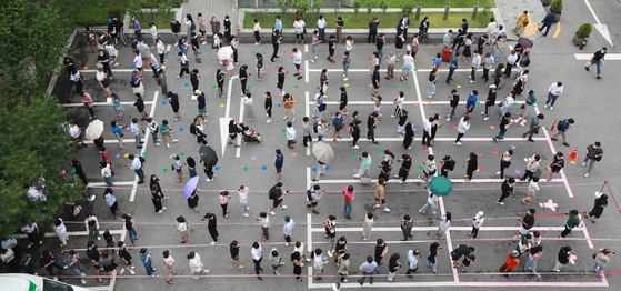 A line forms in front of a public health center in Gangnam District, southern Seoul, as people wait to get tested for Covid-19 on Thursday, when Korea's daily virus cases hit a record 1,275. [YONHAP]