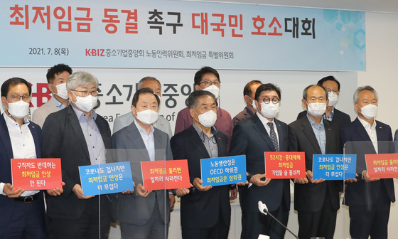 Representatives from the Korea Federation of SMEs call on the government to freeze the minimum wage for 2022 in Seoul on Thursday, holding up signs that say that raising the minimum wage will lead to a decline in hiring. [YONHAP]