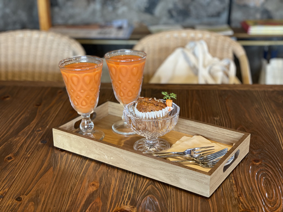 Carrot juice and a cupcake are served at Carrot and Ggannip (Carrot and Perilla Leaf). [LEE SUN-MIN]