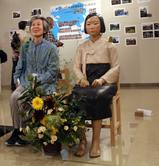 """A visitor to an exhibition featuring a statue symbolizing """"comfort women"""" at Citizen's Gallery Sakae in Nagoya's Aichi Prefecture in Japan poses with the statue on Tuesday, when the exhibition opened. Once scheduled to run through Sunday, the exhibition has been suspended over a delivery of an unidentified explosive on Thursday. [YONHAP]"""