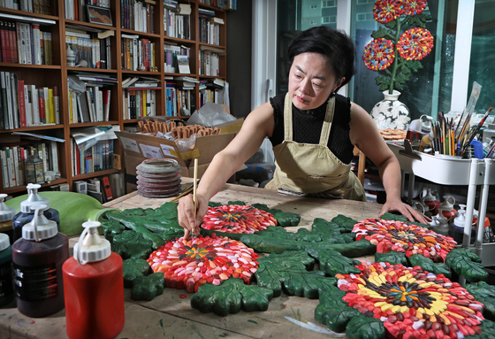 Ceramic artist Lee Ji Sook puts the last layer of color on a flower-shaped terracotta piece in her studio in Anyang, Gyeonggi. [PARK SANG-MOON]