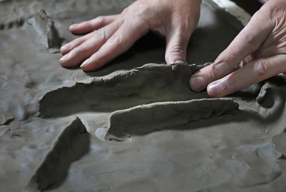 Artist Lee Ji Sook sculpting clay for her chaekgado. [PARK SANG-MOON]