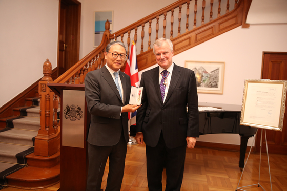 Yun Sang-koo, director of the Rotary Foundation and son of former President Yun Po-sun, left, receives the Order of the British Empire in recognition of services to cultural and educational relations between Britain and Korea at the British Embassy in Seoul on Thursday. Simon Smith, British ambassador to Korea, right, presented the honor. Yun is the eldest son of former President Yun, in whose name an annual conference has been held at the University of Edinburgh on topics pertinent to both Korea and Britain since 2013. The next symposium will be held in Edinburgh in late October 2021, examining the effects of Covid-19 on British and Korean societies. [BRITISH EMBASSY IN SEOUL]
