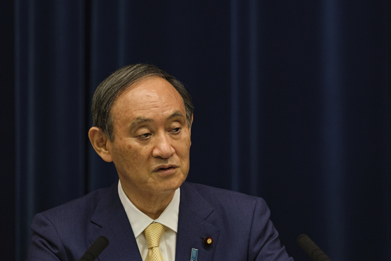 Japan's Prime Minister Yoshihide Suga speaks during a press conference at his residence in Tokyo, Thursday. Suga declared a fourth state of emergency would go in effect on Monday and last through Aug. 22. This means the Olympics, opening on July 23 and running through Aug. 8, will be held entirely under emergency measures.  [AP]