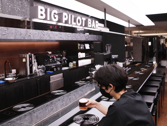 A visitor enjoys a coffee at a new cafe opened on the fifth floor of Lotte Department Store's main branch in Jung District, central Seoul, on Sunday. The new cafe is a collaboration between the retailer, Swedish luxury watchmaker IWC and Seoul-based roastery coffee house Center Coffee. [LOTTE DEPARTMENT STORE]