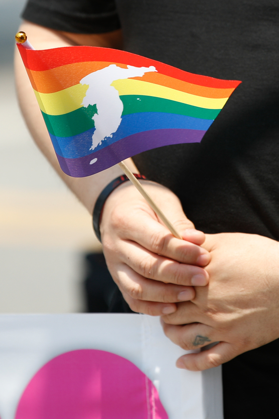 A participant holds a rainbow flag at the 2021 International Day Against Homophobia, Biphobia, Interphobia & Transphobia in Sinchon, western Seoul, on May 22. The event was held under the slogan ″We are here″ and urged the National Assembly to pass an anti-discrimination law this year. [NEWS1]