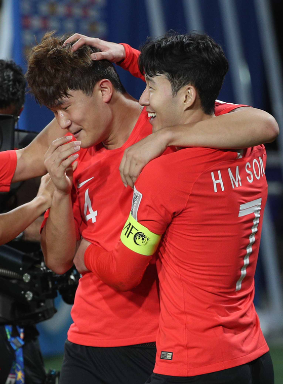 Son Heung-min, right, and Kim Min-jae celebrate after Kim scored a goal for Korea in a game against China at the 2019 AFC Asian Cup in the United Arab Emirates on Jan. 16, 2019. [NEWS1]