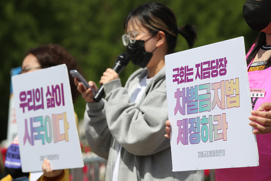 A coalition of women's rights organizations holds a protest outside the National Assembly in western Seoul on May 26 to urge the establishment of an anti-discrimination law. [YONHAP]