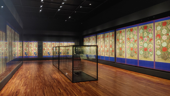 """The final exhibition hall of the National Palace Museum's """"Peonies: Flowers of Peace and Prosperity,"""" is surrounded by folding screens featuring peonies. [JOONGANG ILBO]"""