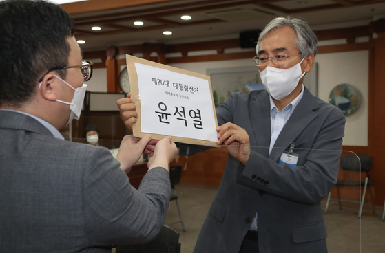 Lee Suk-joon, a key aide to former Prosecutor General Yoon Seok-youl, right, submits Yoon's presidential candidate application to the National Election Commission on Monday.  [NEWS1]