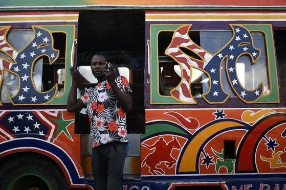 A driver waits for passengers at a bus terminal in Port-au-Prince, Haiti, Saturday, July 10, three days after President Jovenel Moise was assassinated. [AP/MATIAS DELACROIX]