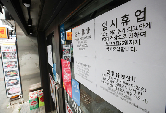 A sign on a restaurant in Myeongdong, one of the busiest areas of central Seoul, announces that it will be closed for two weeks as Seoul and its neighboring areas were put under the strictest social distancing Level 4. [YONHAP]