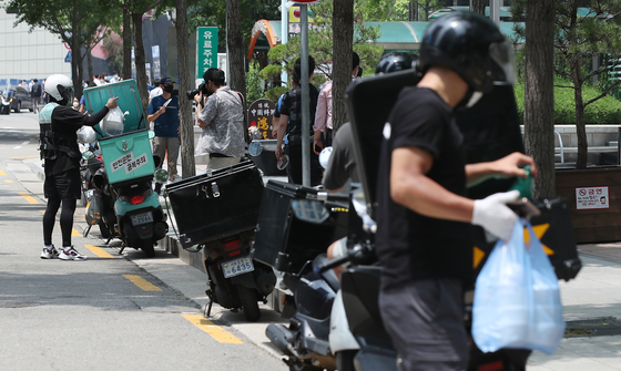Delivery rider motorcycles are parked in Mapo District, western Seoul, on Monday. Monday was the first day of stricter social distancing measures, and food deliveries surged as many stayed indoors to eat. [YONHAP]