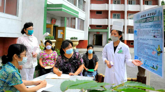 Masked North Koreans review Covid-19 quarantine measures in Moranbong District, Pyongyang, in a photo carried by the North's official Rodong Sinmun Monday as the country strengthens coronavirus prevention efforts. [RODONG SINMUN]