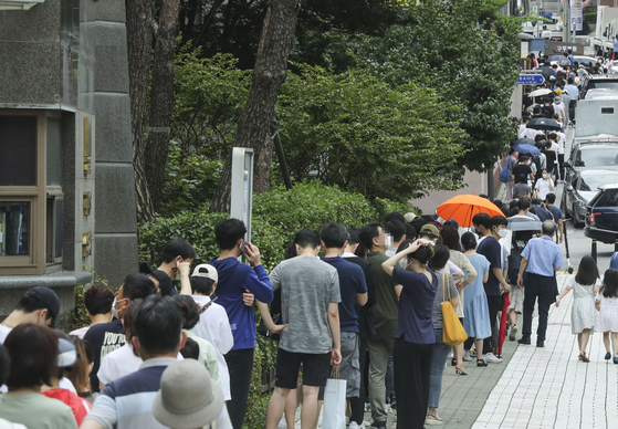 People wait in long lines to get tested for Covid-19 in Gangnam District, southern Seoul, after the country reported its second-largest daily number of new virus cases. [KIM SEONG-RYONG]