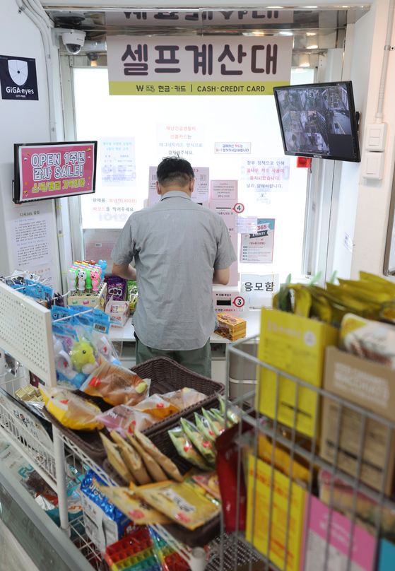 A customer at a convenience store in Songpa District, southern Seoul, uses an automated counter to buy products on Tuesday. Following the government's announcement on Tuesday that it would raise next year's minimum wage by 5.1 percent to 9,160 won ($8), a coalition of convenience store owners released a statement saying they ″cannot pay that amount″ even if they want to. ″We cannot accept a minimum wage raise that does not take into account the realities of convenience owners and other self-employed workers.″ [YONHAP]