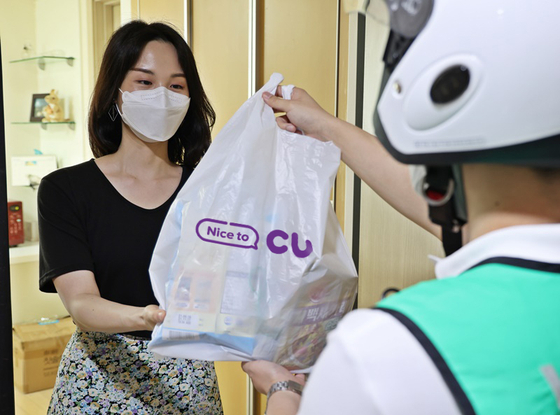 A model receives products she ordered via CU's quick commerce service from a delivery rider. [BGF RETAIL]