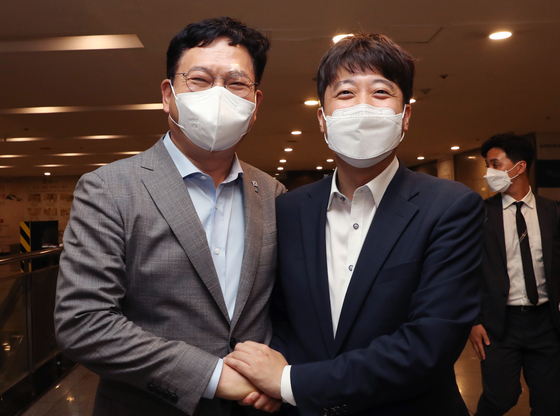 Democratic Party Chairman Song Young-gil, left, and People Power Party Chairman Lee Jun-seok pose after their dinner on Monday.  [YONHAP]