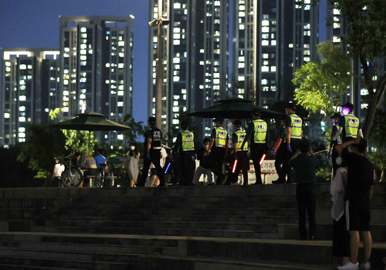 Policemen inspect a park along the Han River in Seoul on Sunday night. Drinking is banned outside in Seoul after 10 p.m. as part of strengthened measures to curb the spread of the coronavirus. [NEWS1]