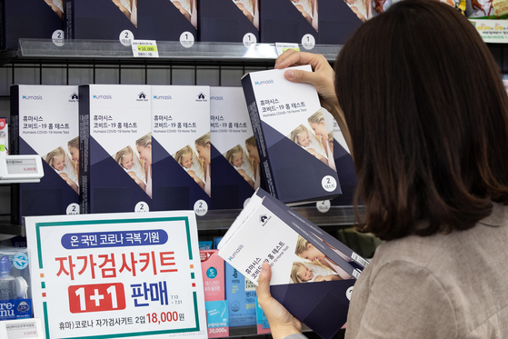 A customer looks through coronavirus self-test kits at a convenience store in Seoul on Wednesday. Convenience store franchise 7-Eleven is running a buy one, get one free promotion on self-test kits through July 31 as daily infection cases in Korea continue to hit new highs. [NEWS1]