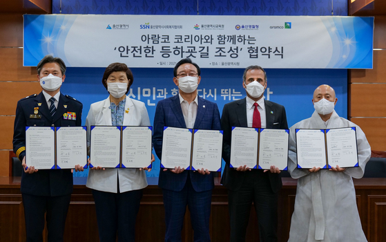 """Song Cheol-ho, mayor of Ulsan, third from left, and Mutib A. Al-Harbi, representative director at Aramco Korea pose for a photo with other stakeholders on Wednesday after signing a partnership agreement on """"Safer Routes to School"""" project at the city hall. [ARAMCO KOREA]"""