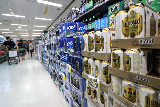 Visitors at a supermarket in Seoul look at alcohol beverages on Wednesday. Sales of wine, beer and makgeolli are rising at supermarkets and convenience stores as more people opt to stay home and drink alone amid the intensified social distancing scheme. [NEWS1]