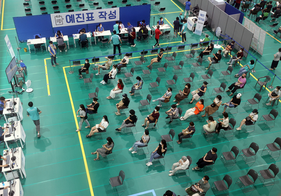 People wait to get vaccinated at a center in Eunpyeong District, northern Seoul on Monday morning. Health authorities said they will resume reservation for the Moderna vaccine for people between the ages of 55 and 59 later in the day. [YONHAP]