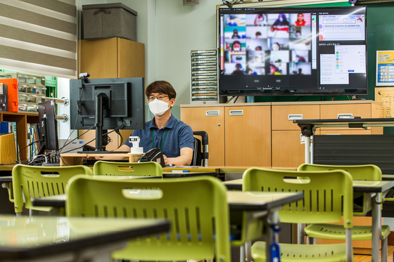 A teacher gives an online class at Muhak Elementary School in northern Seoul on Monday, as all schools in the greater Seoul area switched to online classes due to record-breaking coronavirus infections. Kids will be kept out of classrooms at least through July 25 in Seoul, Gyeonggi and Incheon. [NEWS1]