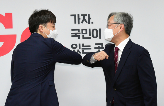 Choe Jae-hyeong, right, former head of the Board of Audit and Inspection, and Lee Jun-seok, chair of the People Power Party, bump elbows at a PPP welcome ceremony on Thursday at its headquarters in Yeouido, western Seoul. [LIM HYUN-DONG]