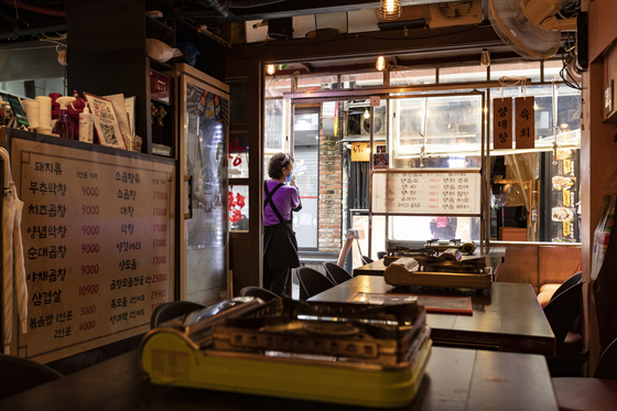 A server waits for customers at a restaurant around Hongdae Station after private gatherings of more than two people are banned from Monday. [JEONG JUN-HEE]