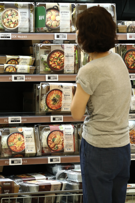 A customer looks at meal kits at a supermarket in Seoul on Thursday. Stricter distancing guidelines have forced people to stay home longer and resulted in an increase of demand for meal kits. [YONHAP]