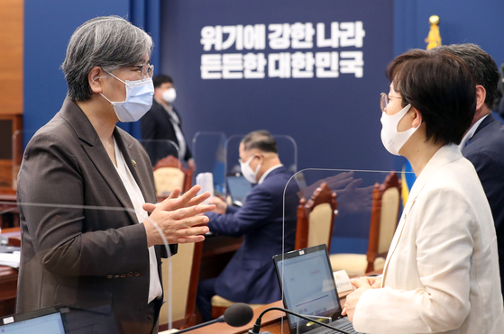 Jung Eun-kyeong, left, head of the Korea Disease Control and Prevention Agency, speaks with Ki Mo-ran, presidential secretary for disease control and prevention affairs, during a Covid-19 response meeting at the Blue House in Seoul on June 7. [YONHAP]